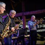 Trzech siwych mężczyzn gra na instrumentach muzycznych - dwóch na saksofonach, a trzeci na puzonie