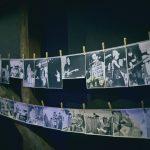 Dwa rzędy czarno-białych fotografii przymocowanych klamerkami na sznurkach