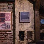 Obrazy w drewnianych ramach zawieszone na ścianach z cegły