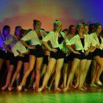 Dziewczyny w białych bluzkach i czarnych krótkich spodeńkach tańczą na scenie