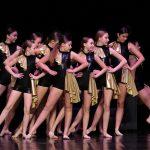 Dziewczyny w czarnych, błyszczących kombinezonach ze złotymi falbankami tańczą na scenie