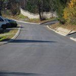 Ulica z nową nawierzchnia asfaltową u wyraźnymi krawężnikami. Po lewej stronie stoi biały bus, a za no samochód osoboy.