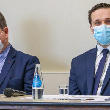 Dwóch mężczyzn w garniturach siedzi przy stoliku.