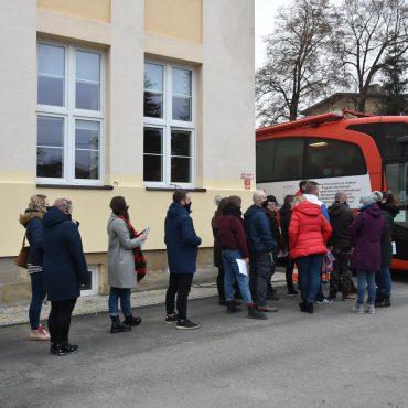 Kolejka kilkudziesięciu ludzi (mężczyzn i kobiet) oczekujących na pobranie krwi w specjalnym do tego przygotowanym autobusie koloru czerwonego.