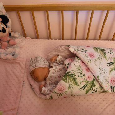 Śpiąca malutka dziewczynka zawinięta w rożek leżąca w łóżeczku drewnianym.