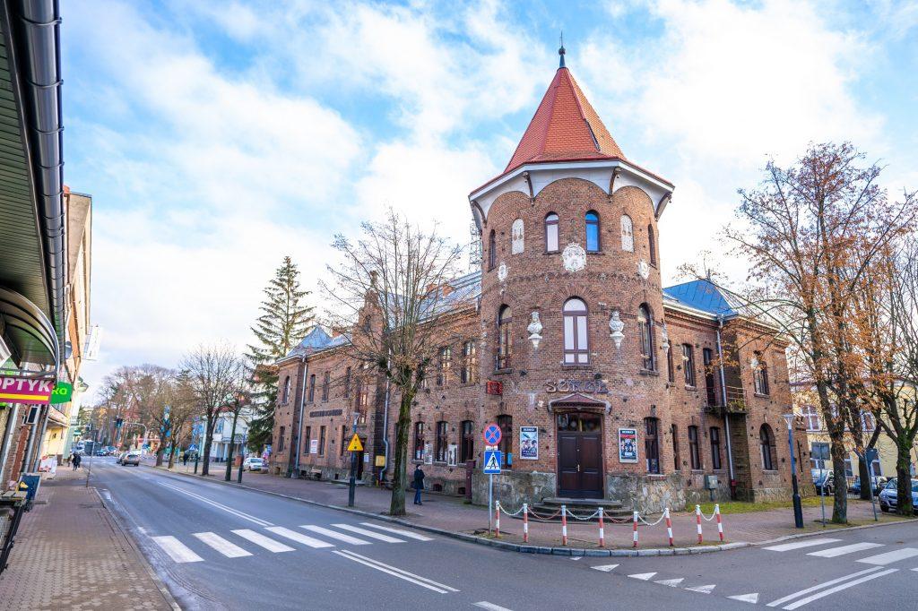 Ogromny budynek z cegły z wieżyczką, znajdujący się przy głównej ulicy.