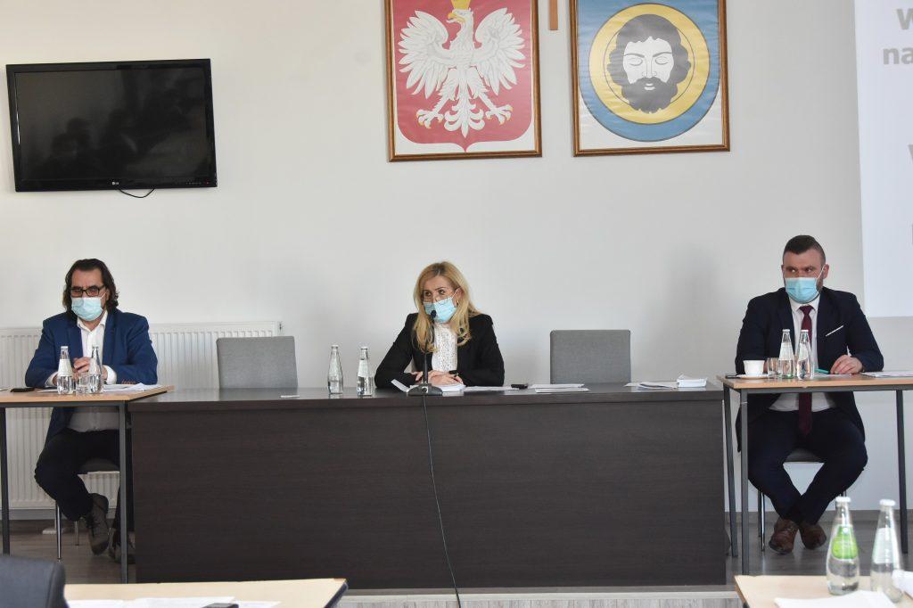 Grupa trzech osób siedzi przy stoliki. Za nimi na ścianie wisi telewizor i obrazy przedstawiające godło Polski i herb Gminy.