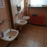Stare umywalki w pomieszczeniu sanitarnym.