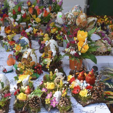 Na stole wyłożonym białym obrusem leżą różnorodne kolorowe pisanki, kurczaki wielkanocne, koszyki, stroiki, książeczki , palmy.