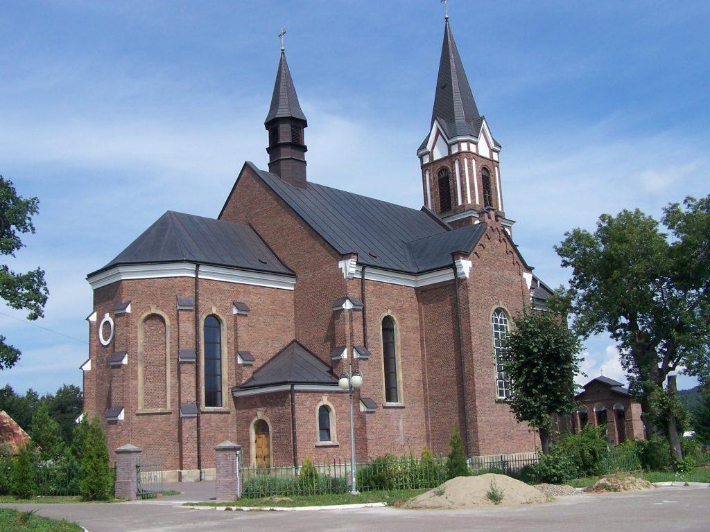 Kościół z ciemnej cegły, dach z szarociemnej blachy, kościół ogrodzony, przed kościołem drzewa liściaste.