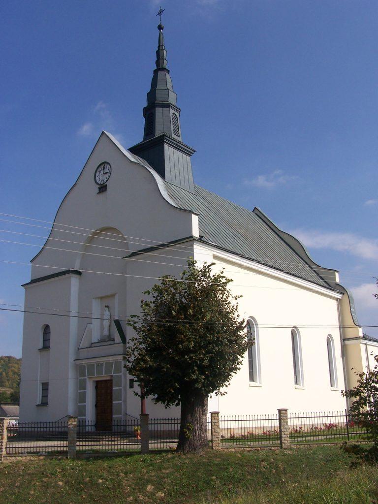 Kościół z jasną elewacją, dach ciemnozielony. Przed budynkiem ogrodzeniem, drzewo liściaste