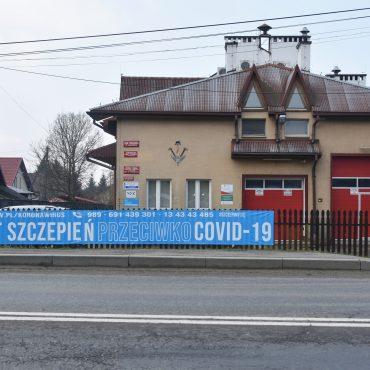 Budynek straży pożarnej z jasną elewacją, z dużymi drzwiami koloru czerwonego. Na ogrodzeniu przed budynkiem rozwieszony duży plakat koloru niebieskiego dot. szczepień.