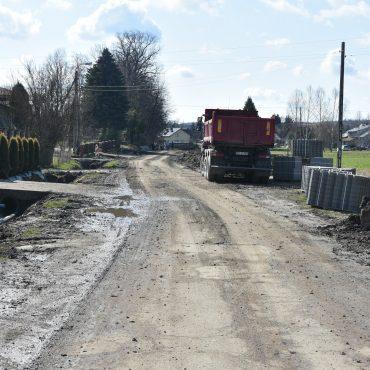 Droga w trakcie przebudowy. Po lewej stronie zabudowa mieszkaniowa, po prawej stronie stoi duża ciężarówka.