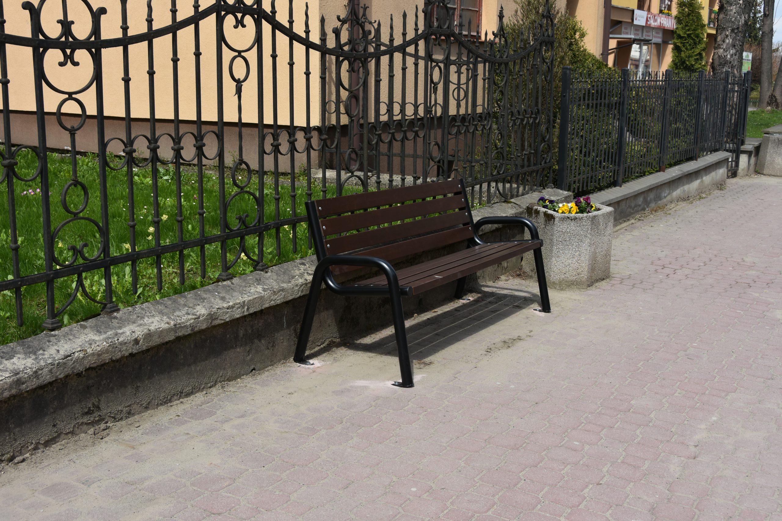Ławka drewniana stoi na chodniku. Za nią ciemne metalowe ogrodzenie. Obok kwietnik.