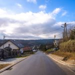 Nowo wyremontowana ulica pomiędzy domami wyłożona asfaltem.
