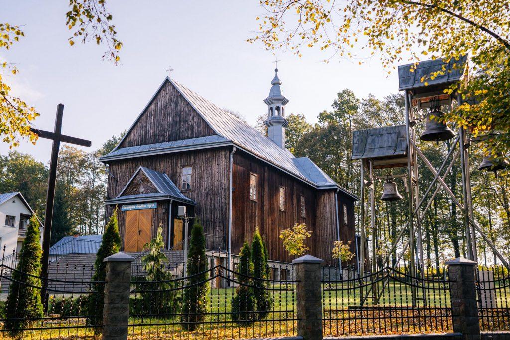 Drewniany kościół, dach blaszany. Kościół ogrodzony metalowym ogrodzeniem.
