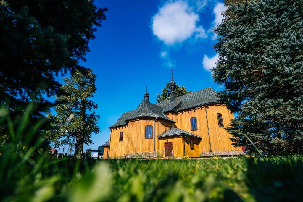 Drewniany kościół, dach blaszany. Przed kościołem liściaste drzewa.
