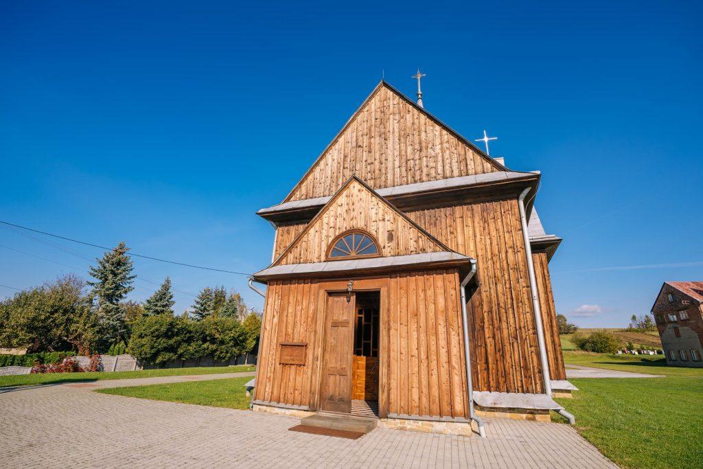 Drewniany kościół, dach blaszany. Przed kościołem plac z kostki brukowej.