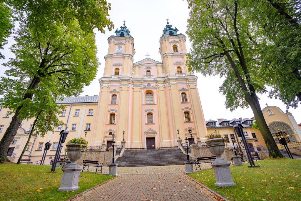 Zabytkowy kościół z jasną elewacją, kryty blaszanym dachem. Przed kościołem duże drzewa liściaste.