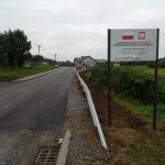Nowo wyremontowana ulica asfaltowa, na poboczu stoi tablica informacyjna z jakich środków została wyremontowana