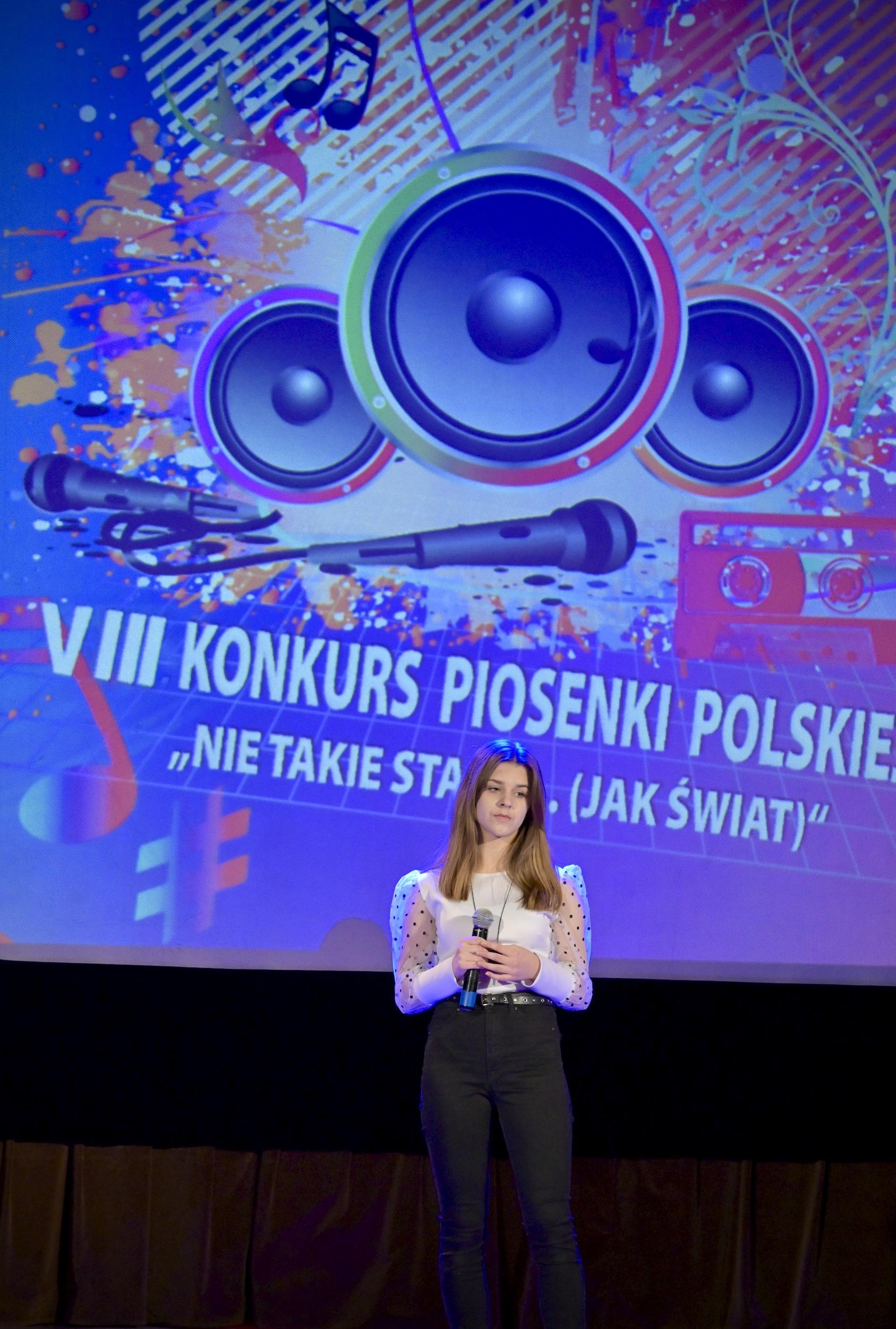 Dziewczyna z ciemnymi włosami, w białej bluzce i ciemnych spodniach śpiewa na scenie. W rękach trzyma mikrofon. Za nią na ekranie wyświetlone logo konkursu.