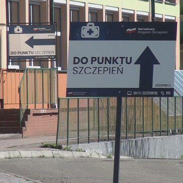 Tabliczka umoeszczona przed budynkiem z napisem do punktu szczepień. Za tabliczką schody do budynku z zieloną barierką. Obok drzewa.