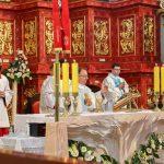 Trzech księży odprawia msze św. Za nimi stoją ministranci w czerwonych sutannach.