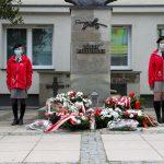 Dwie dziewczyny w czerwonych kurtkach stoją przy pomniku Józefa Piłsudskiego. Przed pomnikiem leżą wiązanki kwiatów. Pomnik stoi przed budynkiem urzędu.