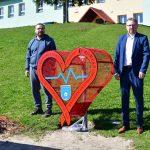 Dwóch mężczyzn stoi obok czerwonego metalowego serca na trawniku. Za nimi budynek szkoły.