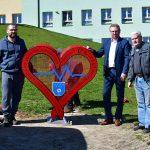 Trzech mężczyzn stoi obok czerwonego metalowego serca na trawniku. Za nimi budynek szkoły.