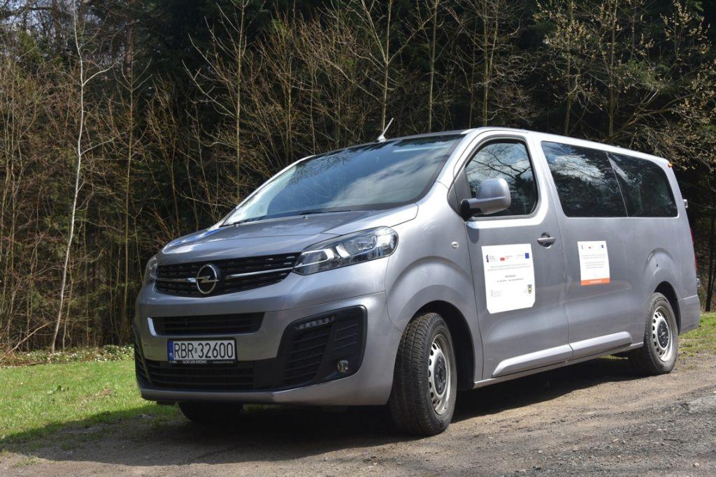 Samochód marki volkswagen kolor srebrny, stoi na tle lasu.