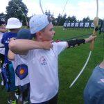 Młody chłopiec ubrany na sportowo w białą koszulkę i czapkę z daszkiem strzela z łuku.