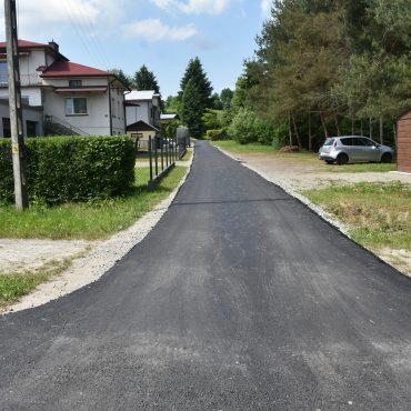 Nowa droga asfaltowa. Po prawej stronie zabudowa rodzinna, po prawej drzewa i krzaki.