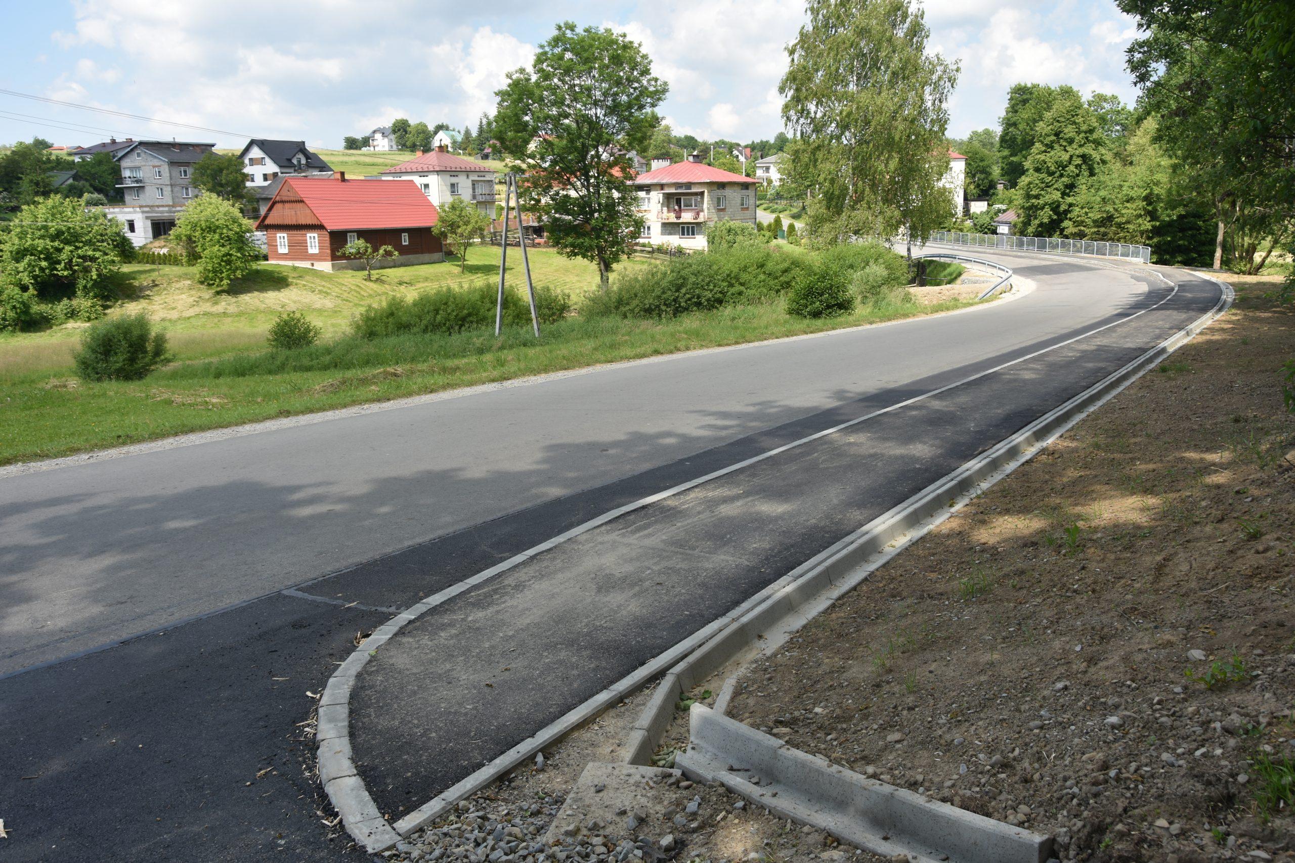 Nowy chodnik wzdłuż drogi asfaltowej. Po lewej stronie tereny zabudowane. .