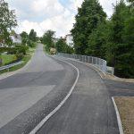 Nowy chodnik wzdłuż drogi powiatowej, w da;szej części po prawej stronie barierki.