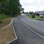 Nowy chodnik wzdłuż drogi powiatowej. Po lewej stronie tereny zielone.