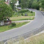 Nowy chodnik wzdłuż drogi powiatowej po prawej stronie. Po lewej stronie tereny zielone z zabudowaniami mieszkalnymi.