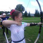 Dziewczynka ubrana na sportowo w białą koszulkę, na włosach gumka czerwona strzela z łuku.