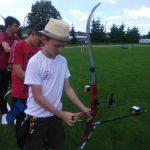 Grupa dzieci - chłopców ubrana na sportowo przygotowuje się do strzału z łuku.