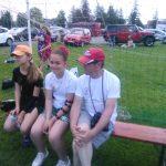 Trzy osoby - dwie dziewczyny i chłopak siedzą na ławce, Za nimi bramka do piłki nożnej.