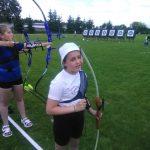 Dziewczynka ubrana na sportowo przygotowuje się do strzału z łuku na zewnątrz.