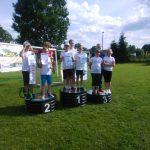 Grupa dzieci ubrana na sportowo na świezym powietrzu stoi na podium z dyplomami.