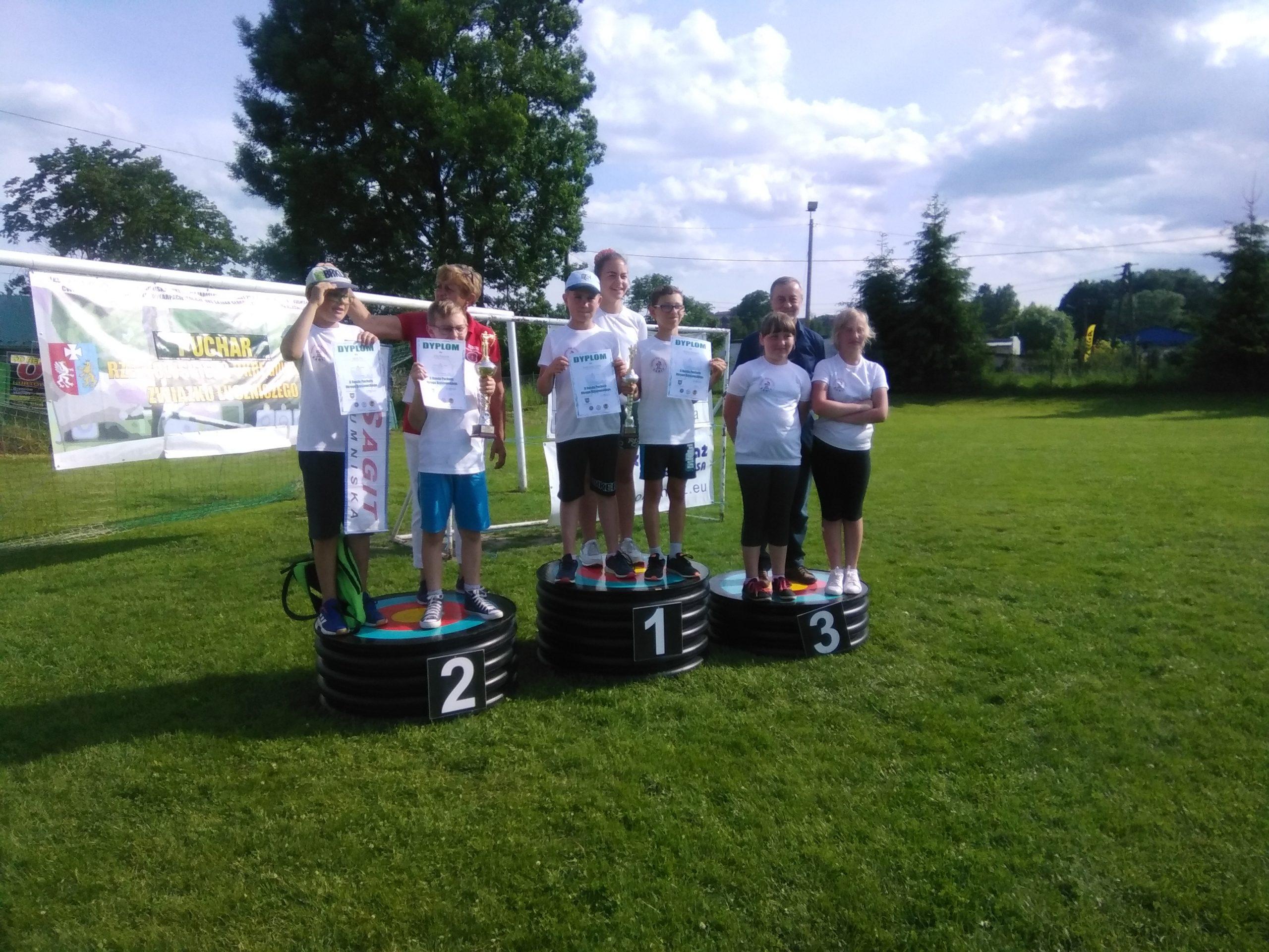 Grupa dzieci ubrana na sportowo stoi na podium z medalami na zewnątrz.