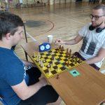 Dwóch mężczyzn gra w szachy na sali gimnastycznej.