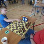Młody chłopak i starszy mężczyzna grają w szachy na sali gimnastycznej.