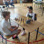 Dziewczynka i chłopiec grają w szachy przy stoliku na sali gimnastycznej.