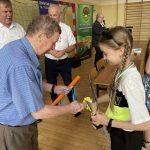 Starszy mężczyzna w niebieskiej koszuli wręcza dziewczynce z warkoczykami drobne gadźety za udział w turnieju.