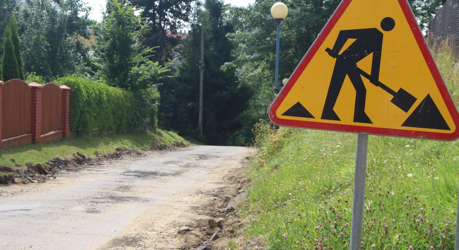 Znak drogowy - ulica w remoncie. W tle droga nadajaca się do remontu.