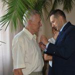 Mężczyzna w garniturze odznacza starszego mężczyzne.
