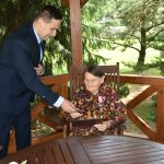 Mężczyzna w garniturze przekazuje wyróżnienie starszej kobiecie.